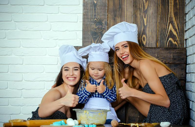 Pojke och flickor i kockhattar som ger upp tummar arkivbild
