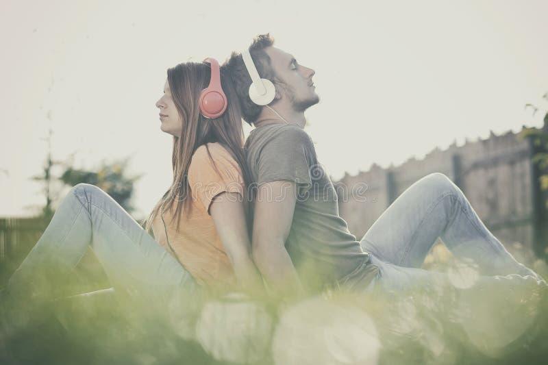 Pojke och girll som lyssnar till musik arkivbild