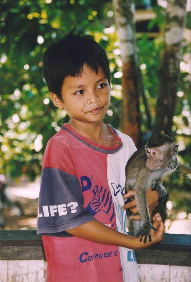 Pojke och hans apavän i Kalimantan, Indonesien royaltyfri bild
