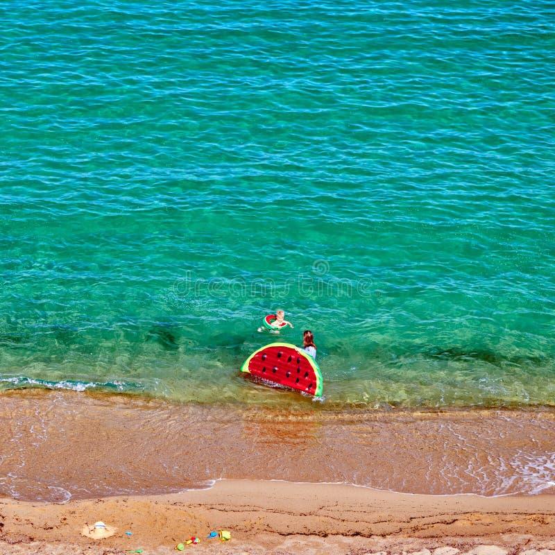 Pojke och hans moder på stranden med den uppblåsbara flötet royaltyfria bilder