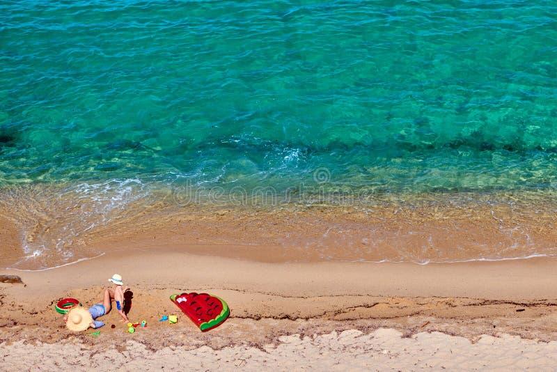Pojke och hans moder p? stranden med den uppbl?sbara fl?tet royaltyfria bilder