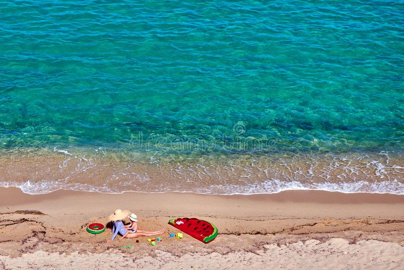 Pojke och hans moder p? stranden med den uppbl?sbara fl?tet arkivfoton