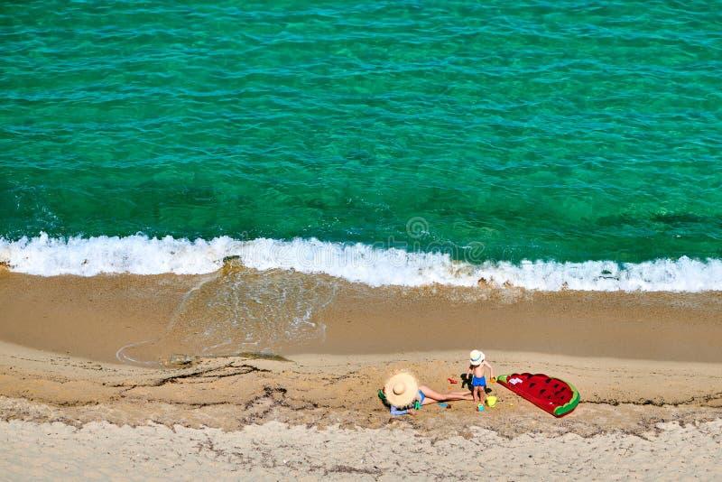 Pojke och hans moder p? stranden med den uppbl?sbara fl?tet royaltyfri foto