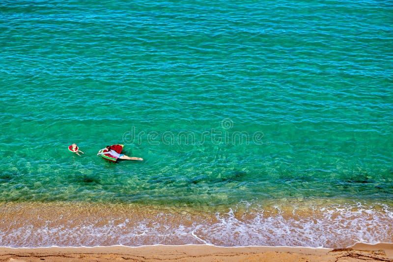 Pojke och hans moder p? stranden med den uppbl?sbara fl?tet royaltyfri bild