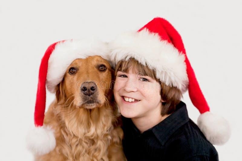 Pojke och hund i julhattar royaltyfria foton