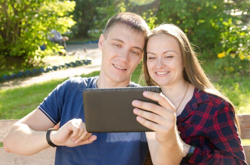 Pojke och le flickapratstund över internet på en minnestavla med vänner arkivbild