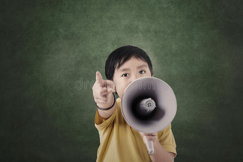 Pojke och megafon framme av det tomma brädet royaltyfri bild