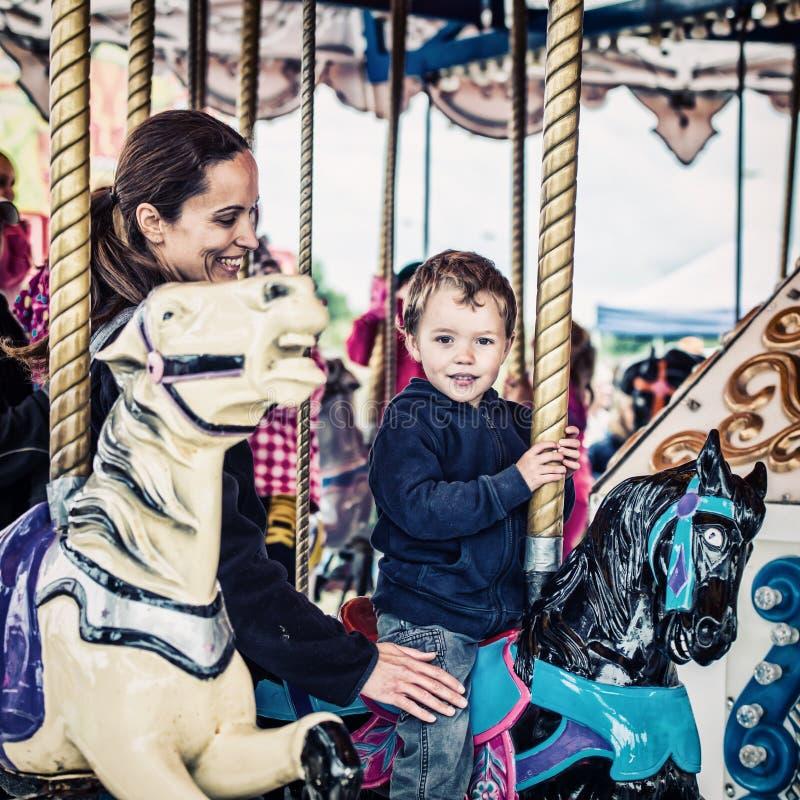 Pojke och moder på den Retro karusellen tillsammans - royaltyfri bild