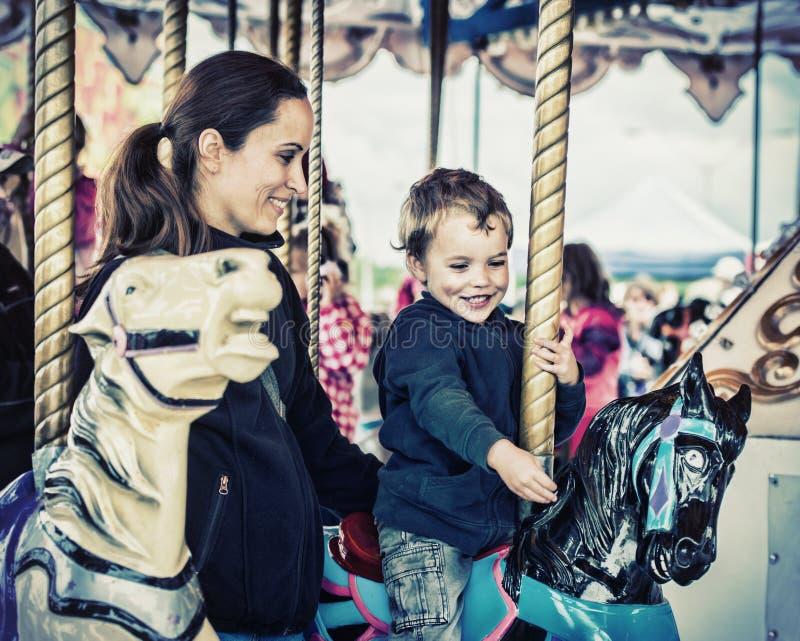 Pojke och moder tillsammans på en Retro karusellritt - royaltyfria foton