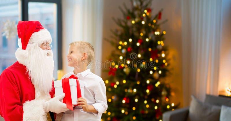 Pojke och santa med julgåvor hemma fotografering för bildbyråer