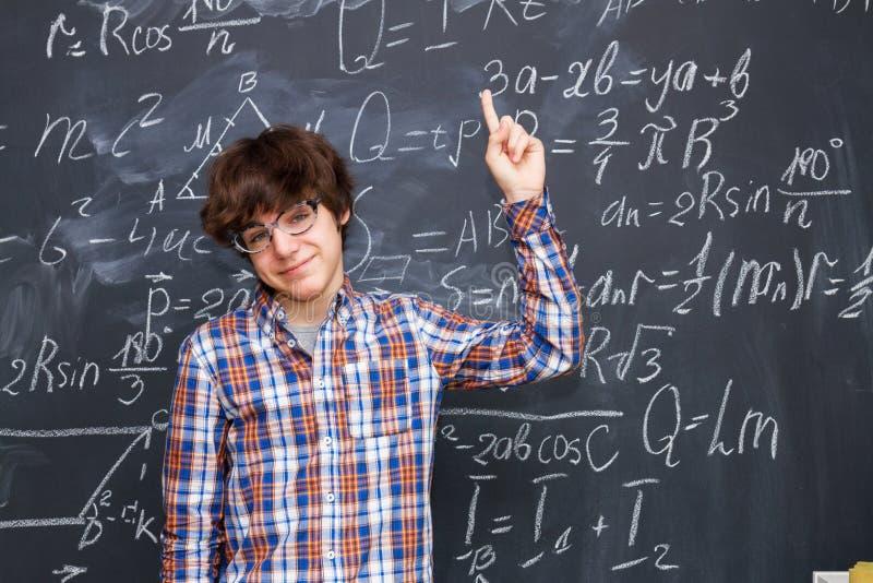 Pojke och svart tavla som fylls med matematikformler royaltyfri bild