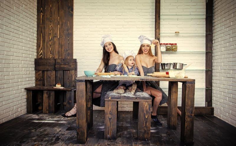 Pojke och två flickor som sitter på köksbordet royaltyfria foton