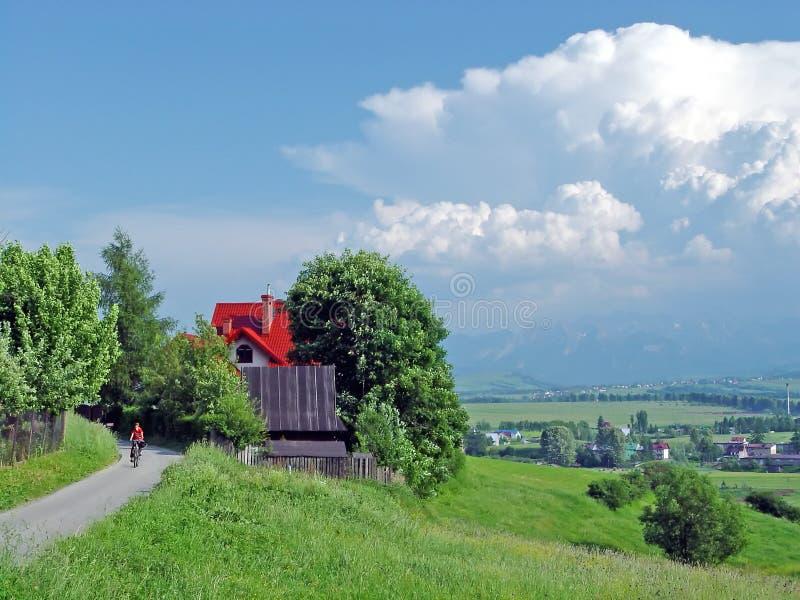 Pojke på cykeln i bergby i sommar arkivfoto