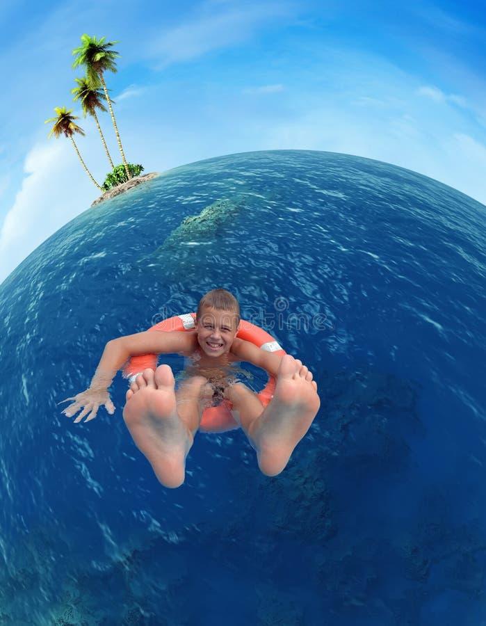 Pojke på en livboj som svävar på havet arkivfoton