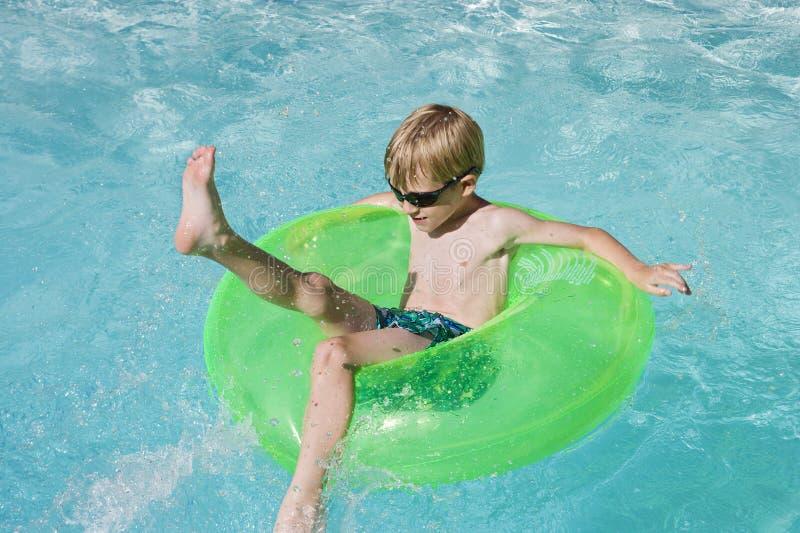 Pojke på flöteröret i simbassäng royaltyfri foto