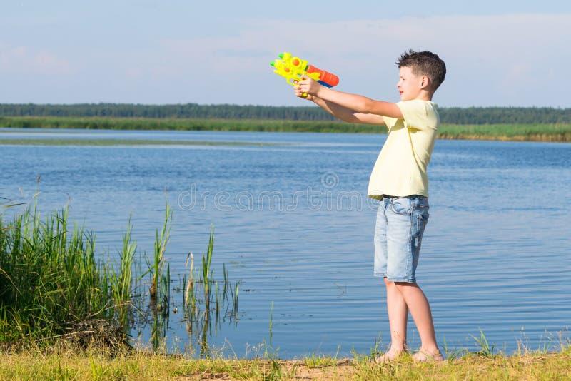 Pojke på floden som spelar med ett vattenvapen royaltyfri fotografi