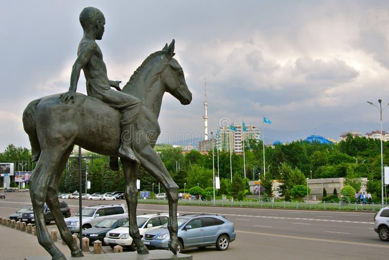 Pojke på häststatyn och den centrala gatan av Almaty arkivfoto