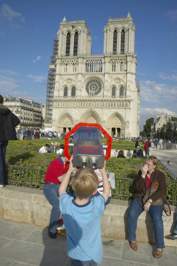Pojke på kikare som ser Notre Dame Cathedral, Paris, Frankrike royaltyfri fotografi