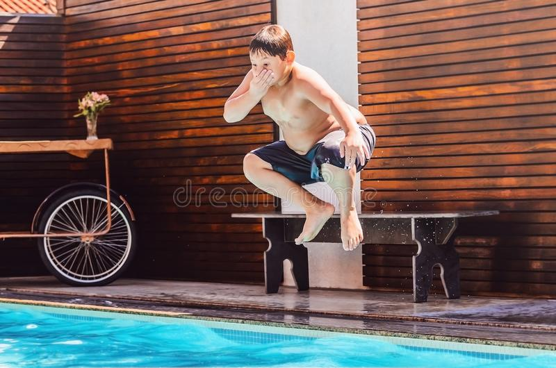 Pojke på luftbanhoppningen in i simbassängen arkivfoto