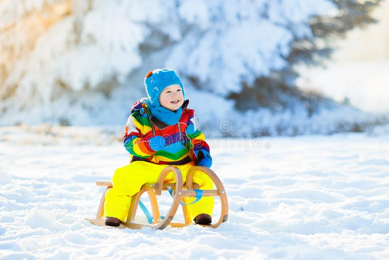 Pojke på släderitt Sledding för barn Unge med pulkan arkivbild