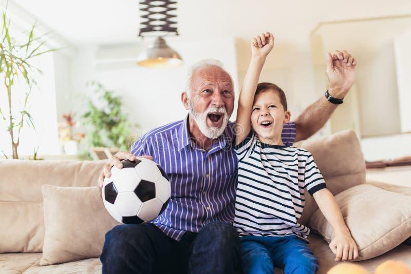 Pojke på soffan med farfarbifallet för en fotbollgam arkivbild