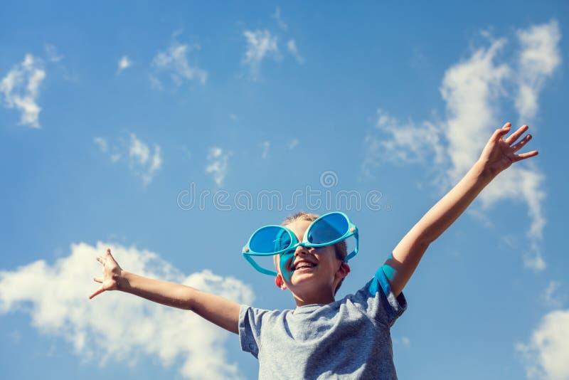 Pojke på stranden med stor solglasögon som tycker om solen arkivfoto