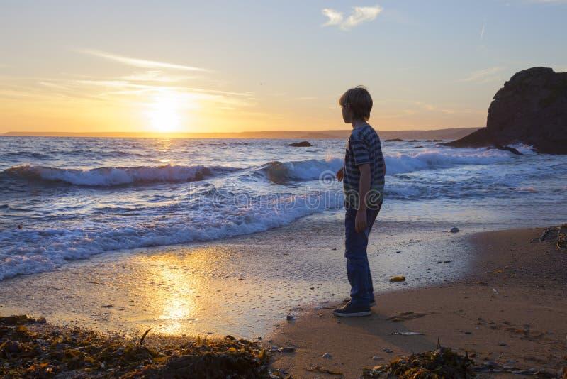 Pojke på stranden på solnedgången, Devon, England royaltyfria bilder