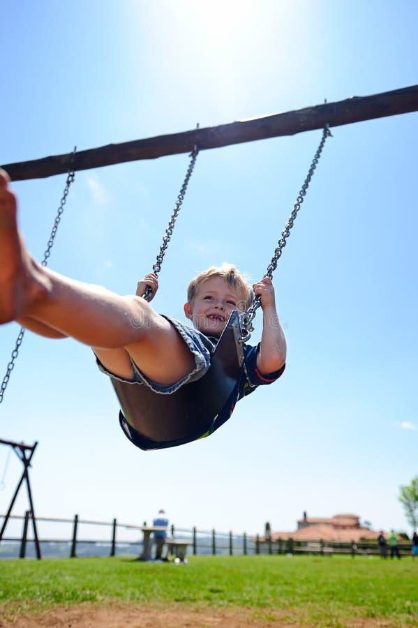 Pojke på swing royaltyfria foton