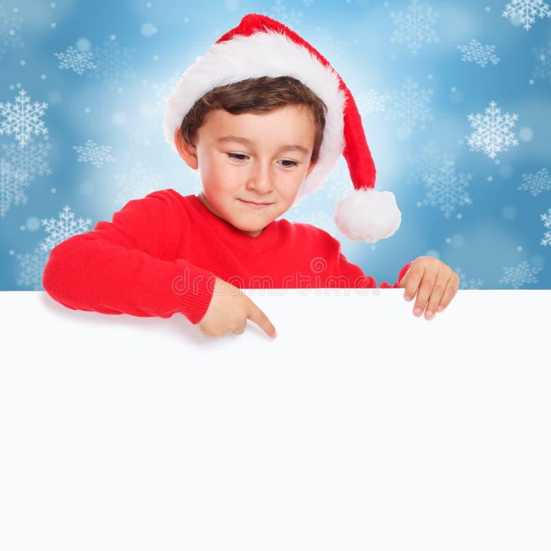 Pojke Santa Claus som för julbarnunge pekar tom banerteckencopyspace fotografering för bildbyråer