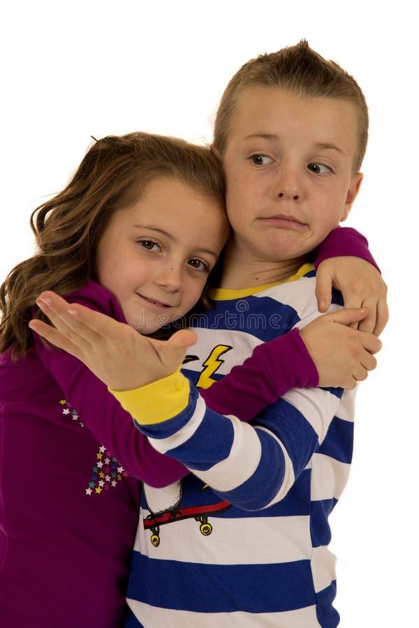 Pojke som är rädd av en flickas pyjamas för vinter för kram bärande royaltyfri foto
