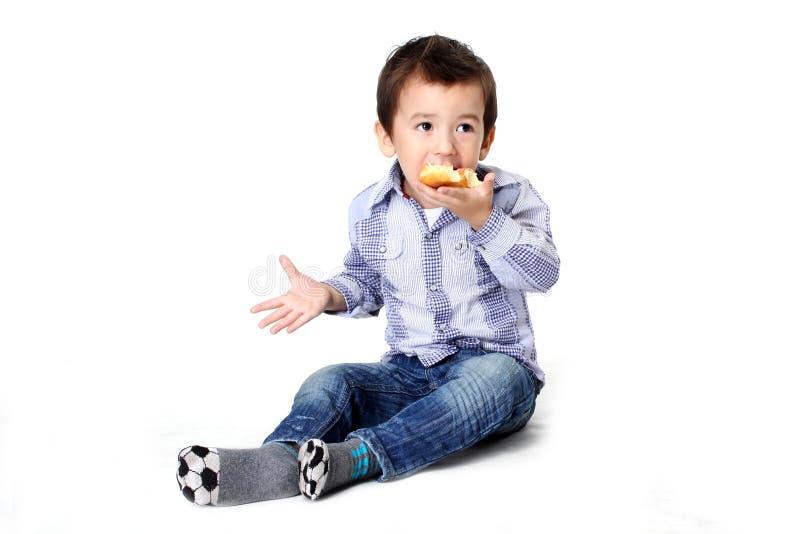 Pojke som äter degmuttern royaltyfri foto
