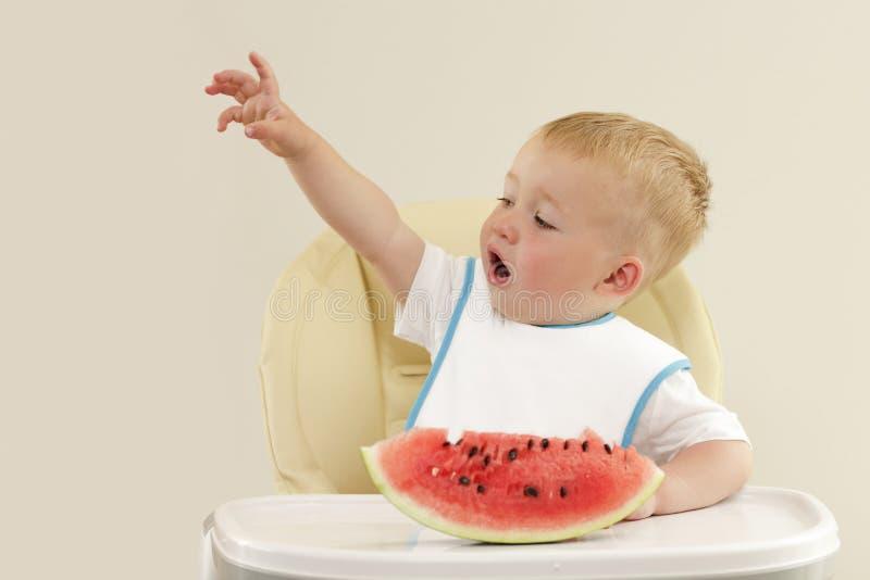 pojke som äter den små vattenmelonen royaltyfria bilder