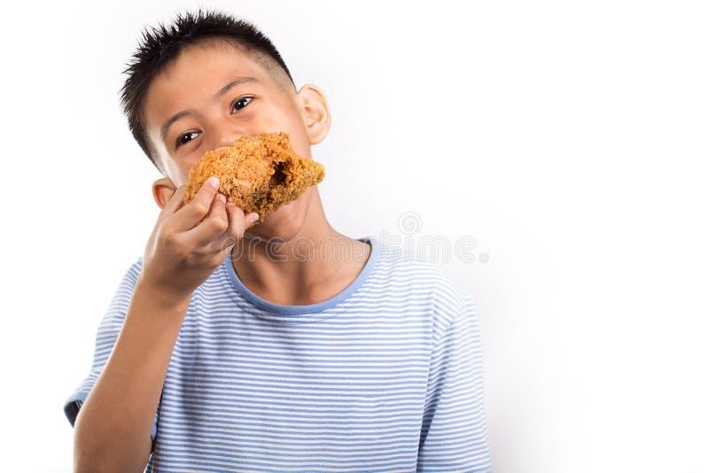Pojke som äter en djup stekt kyckling royaltyfri fotografi