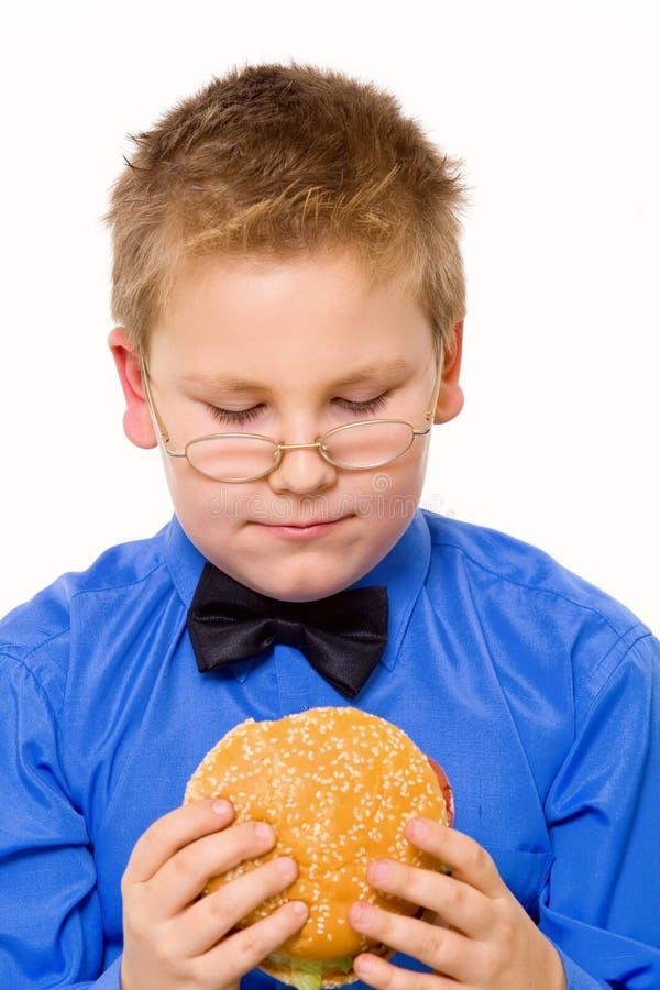 pojke som äter hamburgareskolabarn arkivbild