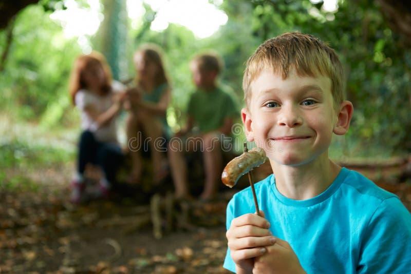 Pojke som äter korven runt om läger med vänner fotografering för bildbyråer
