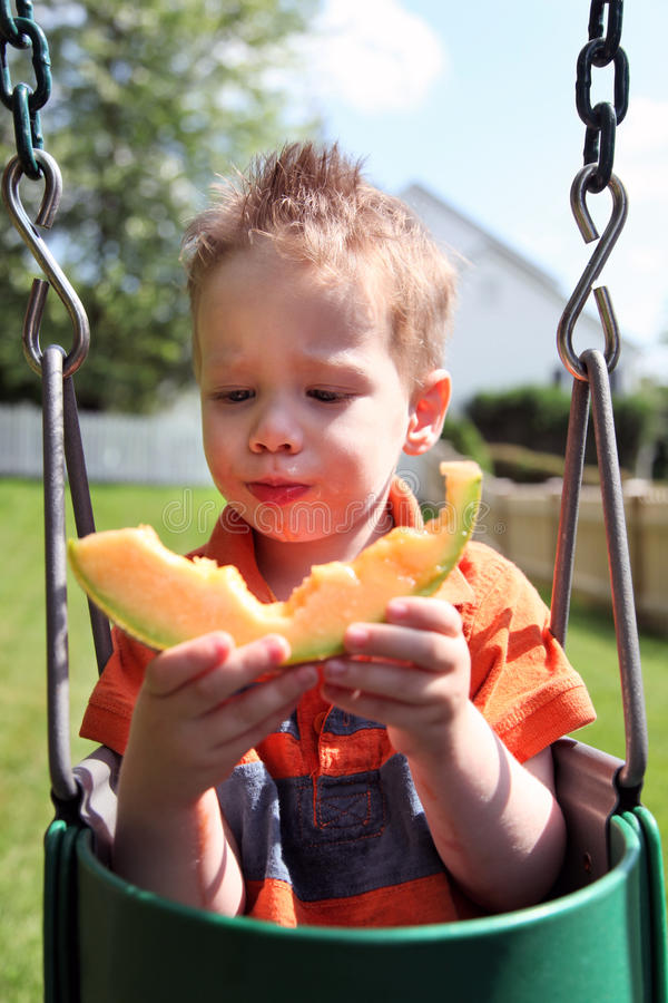 pojke som äter melonen arkivbilder