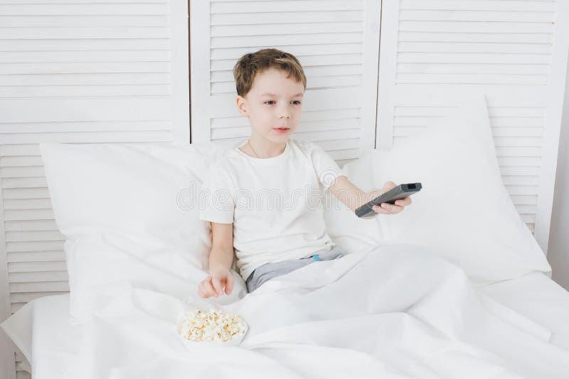 Pojke som äter popcorn som sitter i säng- och hålla ögonen påTV royaltyfria bilder