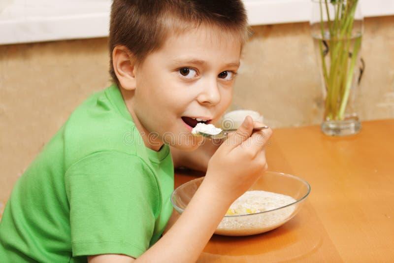 pojke som äter porridge royaltyfria bilder