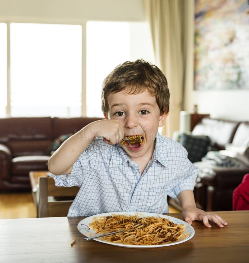 Pojke som äter spagetti arkivfoto