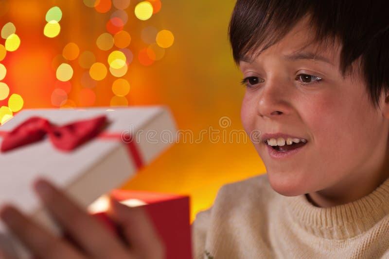 Pojke som öppnar hans närvarande för jul med förväntan fotografering för bildbyråer