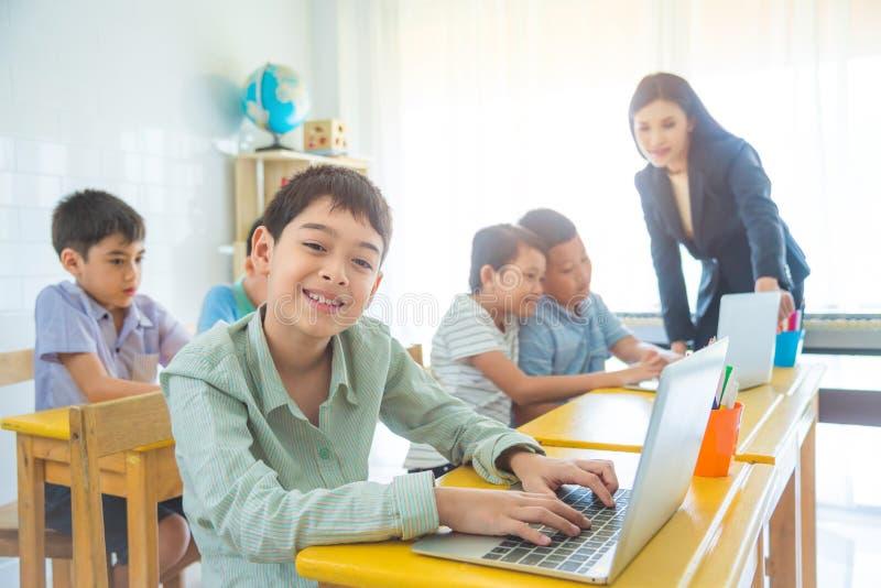 Pojke som använder bärbar datordatoren och leenden i klassrum royaltyfri fotografi
