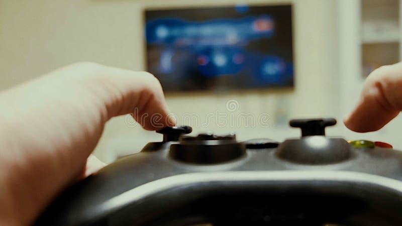 Pojke som använder en kontrollant för att spela en videospel royaltyfria bilder