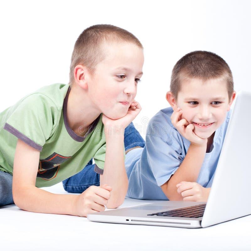 Pojke som använder en modern bärbar datordator, medan ligga på golvet royaltyfria bilder