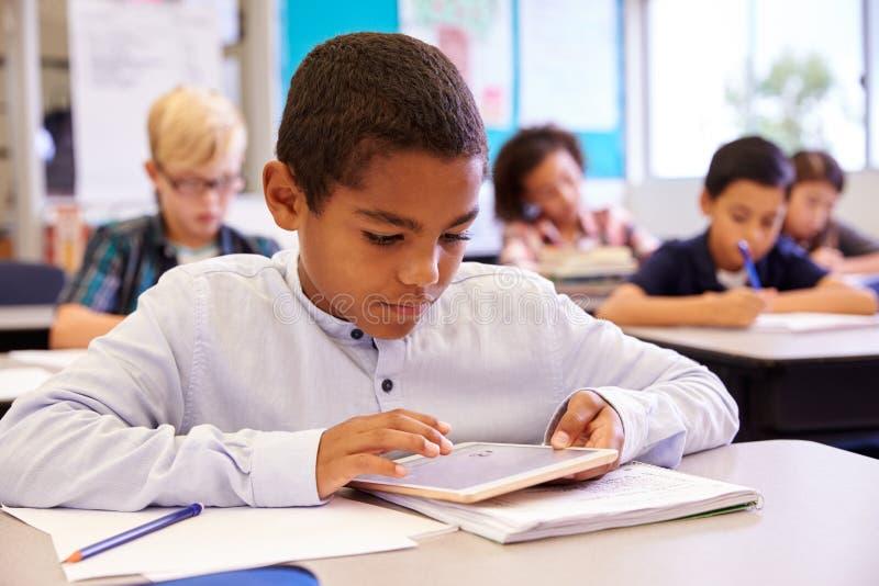 Pojke som använder minnestavladatoren i grundskolagrupp arkivfoto