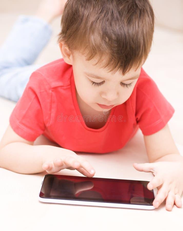Download Pojke Som Använder Minnestavlan Fotografering för Bildbyråer - Bild av ligga, mänskligt: 37349013