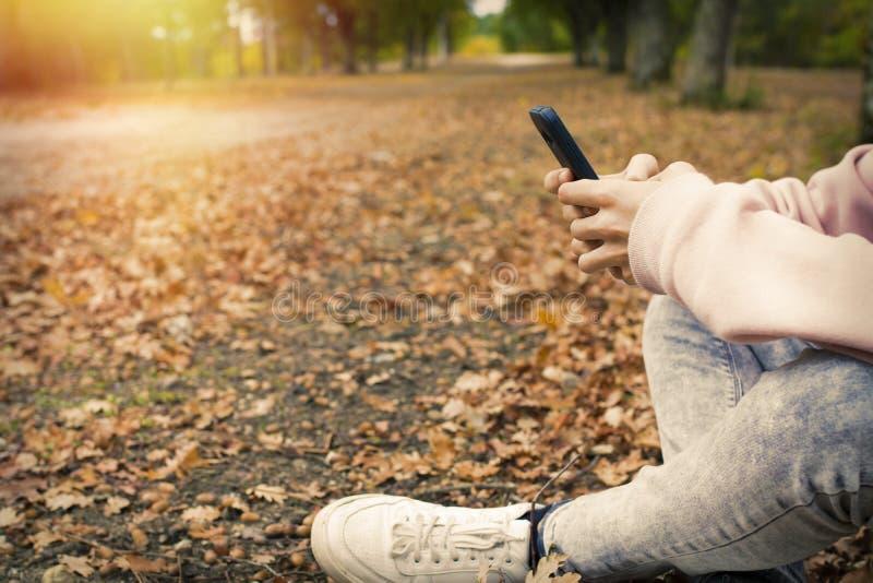 Pojke som använder smartphonen på sida av vägen royaltyfri fotografi