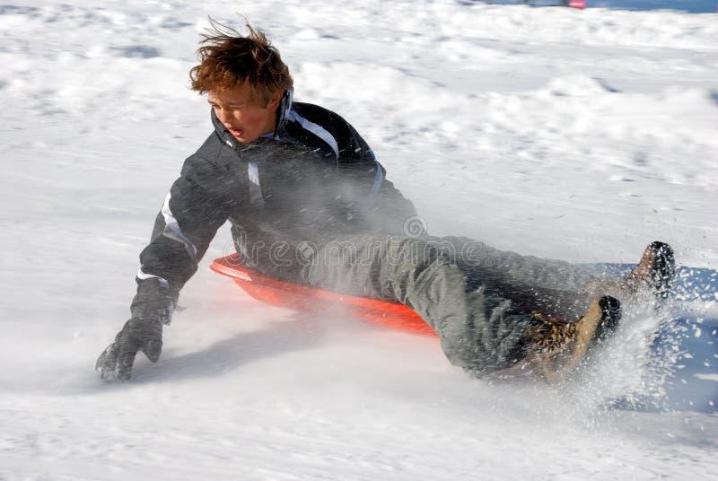 pojke som bromsar ner kullsleden som sledding arkivbild