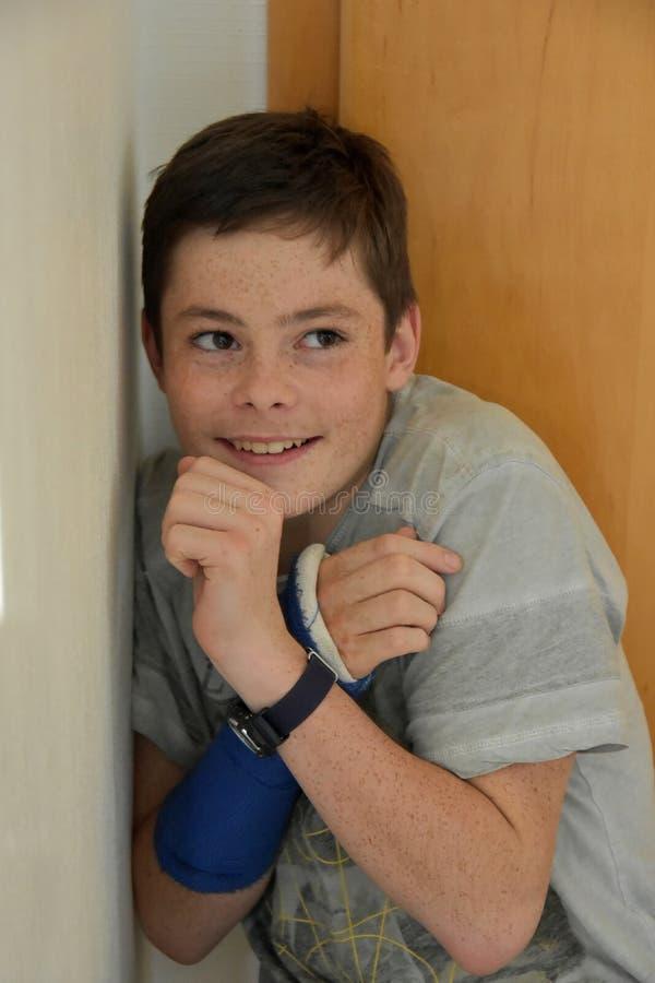 Pojke som döljas i hörnet av ett rum royaltyfri foto