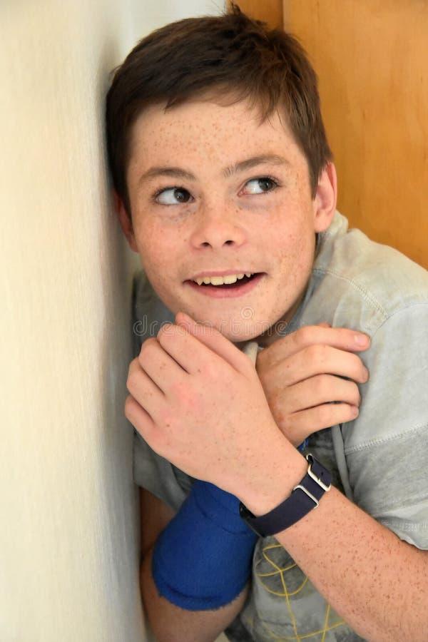 Pojke som döljas i hörnet av ett rum arkivfoton