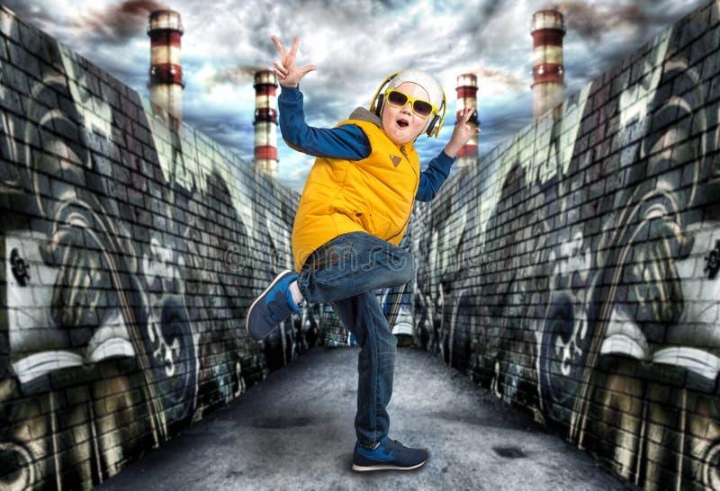 Pojke som dansar Hip Hop Mode för barn` s Den unga rapparen Grafitti på väggarna Kyla rap dj royaltyfri bild